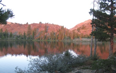 The mountains on the other side of the lake are all a bright pink.
